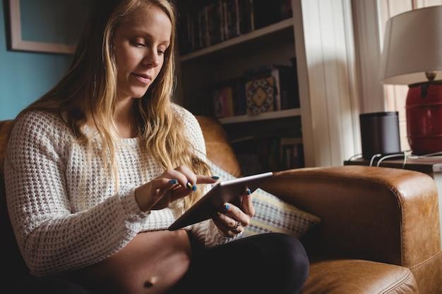 Schwangere frau, die digitale tablette im wohnzimmer verwendet