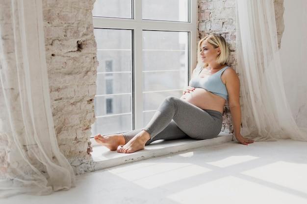 Schwangere frau, die durch das fenster schaut