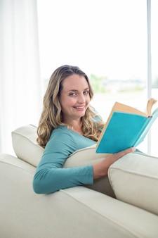 Schwangere frau, die ein buch auf der couch liest