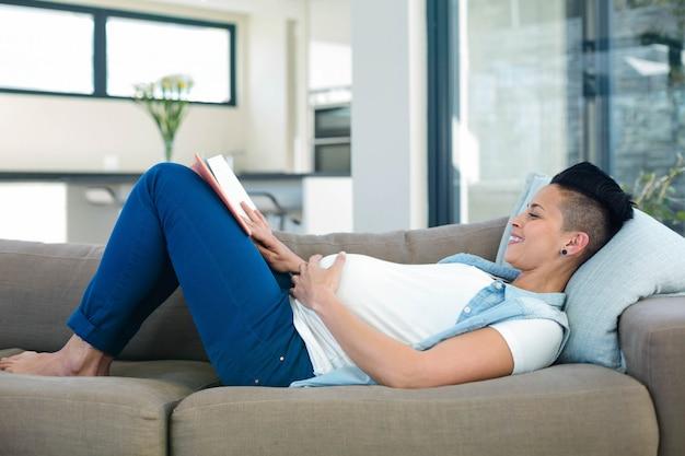 Schwangere frau, die ein buch beim lügen auf sofa im wohnzimmer liest
