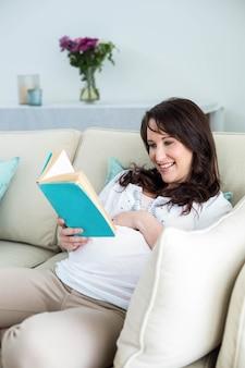 Schwangere frau, die ein buch im wohnzimmer liest