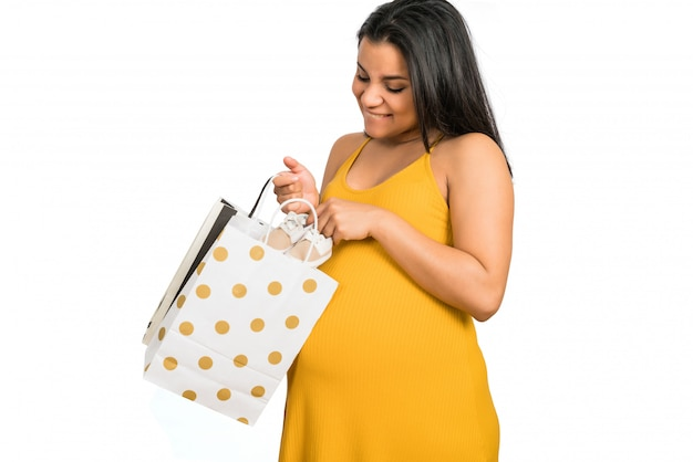 Schwangere frau, die ein geschenk für neues baby öffnet.