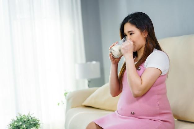 Schwangere frau, die ein glas milch auf sofa im wohnzimmer trinkt