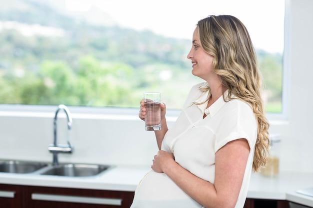 Schwangere frau, die ein glas wasser in der küche trinkt