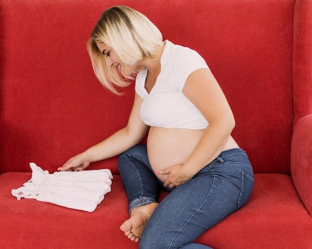 Schwangere frau, die ein kleines kleid betrachtet