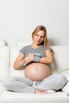 Schwangere frau, die ein medizinisches gerät verwendet
