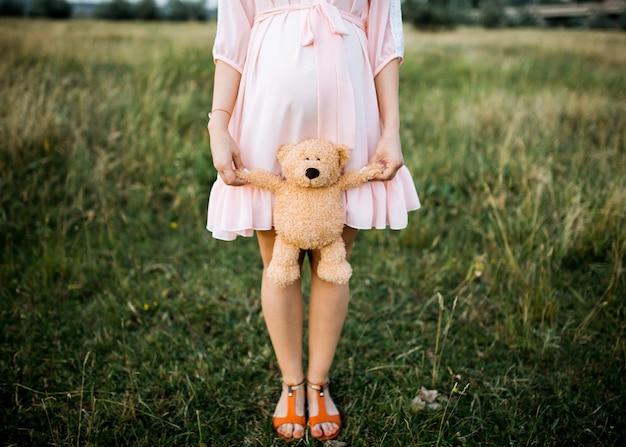 Schwangere frau, die ein plüschbärenspielzeug hält