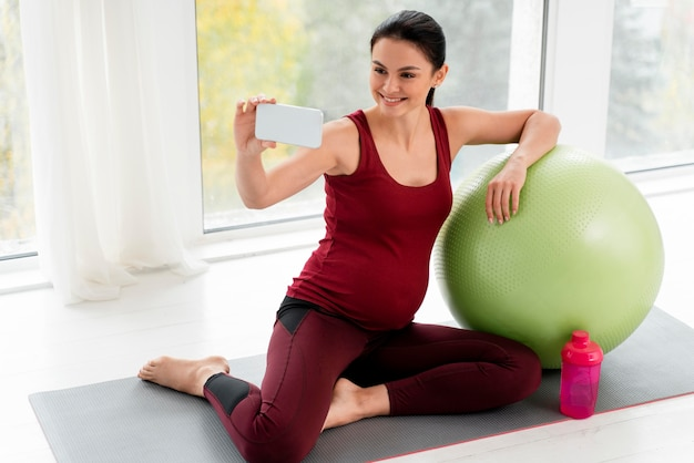 Schwangere frau, die ein selfie neben einem fitnessball nimmt