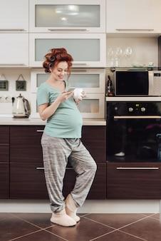 Schwangere frau, die ein smartphone verwendet, das in der küche steht