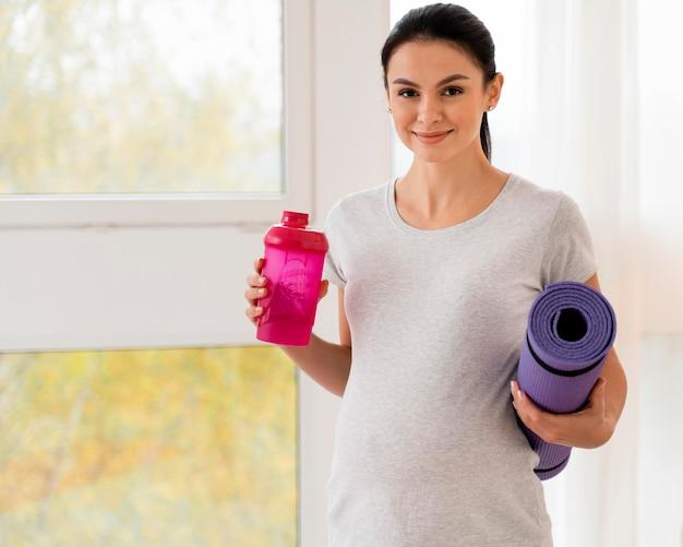 Schwangere frau, die eine eignungsmatte und eine flasche wasser mit kopienraum hält