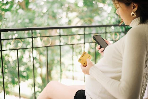 Schwangere frau, die eine kreditkarte hält und handy für das on-line-einkaufen verwendet