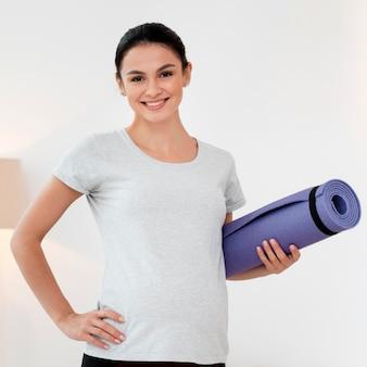 Schwangere frau, die eine lila fitnessmatte hält