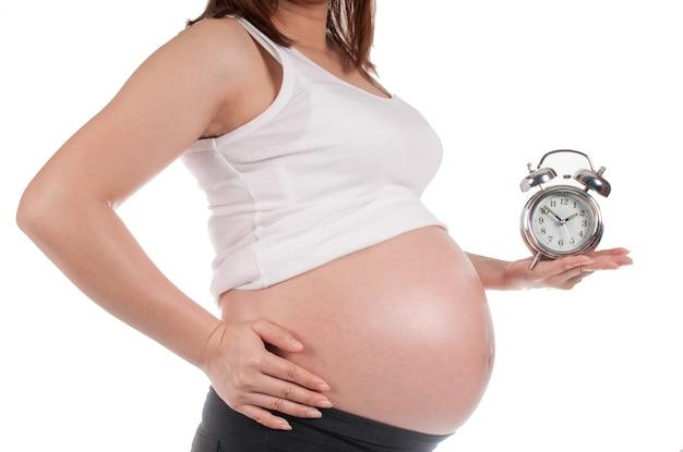 Schwangere frau, die eine uhr wartet auf die geburt hält