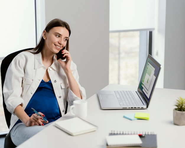 Schwangere frau, die einen anruf bei der arbeit hat