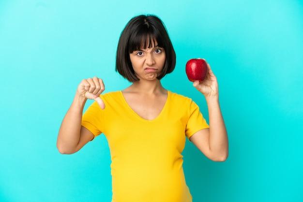Schwangere frau, die einen apfel hält, der auf blauem hintergrund isoliert ist und daumen nach unten mit negativem ausdruck zeigt