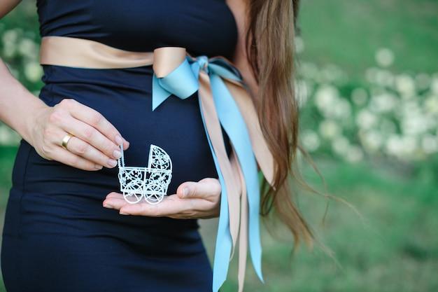 Schwangere frau, die einen spielzeugkinderwagen hält