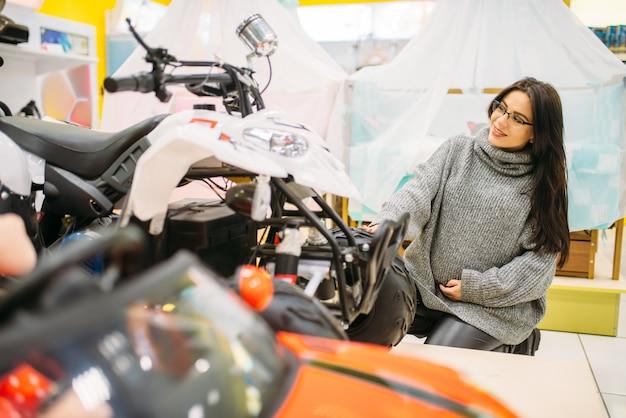 Schwangere frau, die elektroauto im spielzeugladen wählt