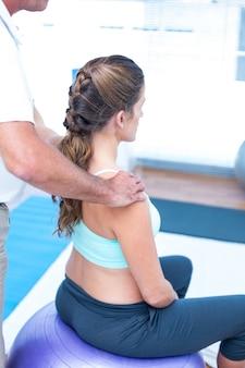 Schwangere frau, die entspannende massage an der turnhalle hat