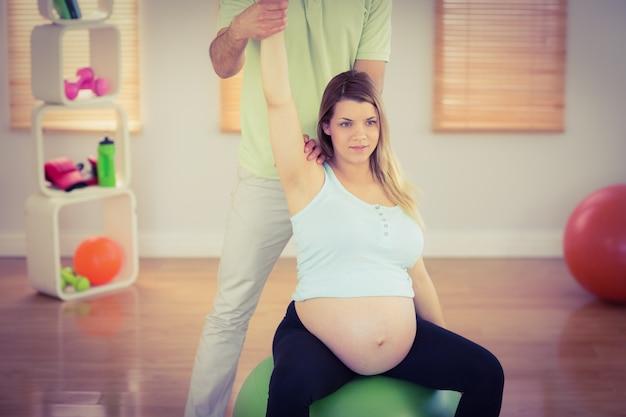 Schwangere frau, die entspannende massage beim sitzen auf übungsball hat