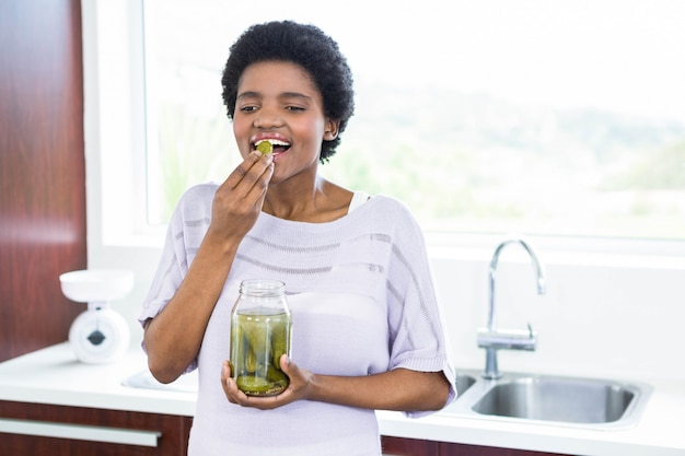 Schwangere frau, die essiggurken in der küche isst