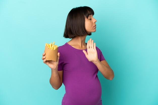 Schwangere frau, die gebratene chips über isoliertem hintergrund hält, stopp-geste macht und enttäuscht