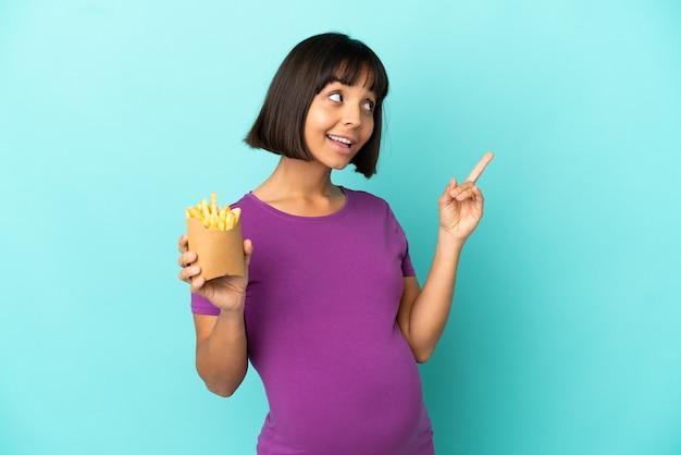 Schwangere frau, die gebratene chips über isoliertem hintergrund hält und auf eine großartige idee hinweist