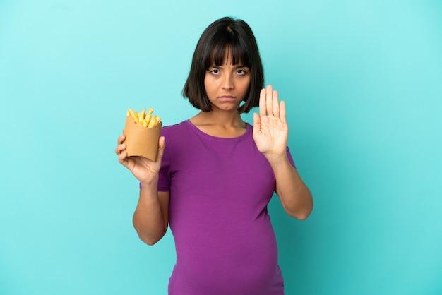 Schwangere frau, die gebratene chips über isoliertem hintergrund hält und stopp-geste macht
