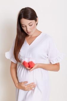 Schwangere frau, die gestrickte babyschuhe hält und es betrachtet