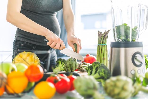 Schwangere frau, die gesundes lebensmittel kocht