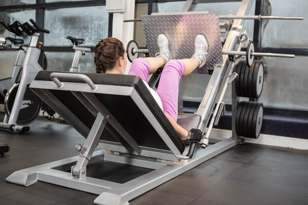 Schwangere frau, die gewichtsmaschine an der turnhalle verwendet