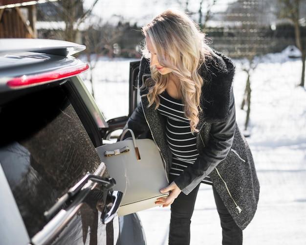Schwangere frau, die handtasche vom auto nimmt