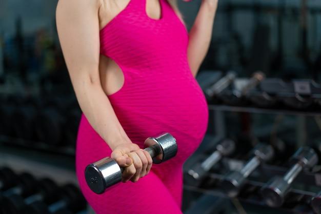 Schwangere frau, die hanteln, die bizepsmuskel an der turnhalle anheben, die nahe spiegel steht schwangerschaft, gesunder lebensstil, sport- und fitnesskonzept kaukasisches weibliches athletentraining