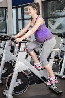Schwangere frau, die hometrainer an der turnhalle verwendet