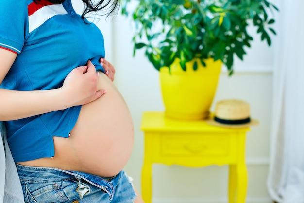 Schwangere frau, die ihr bauchstudio-hintergrundfoto hält.