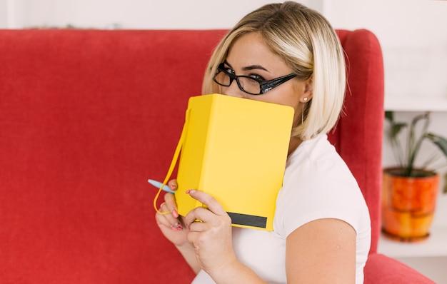 Schwangere frau, die ihr gesicht mit einem notizbuch bedeckt