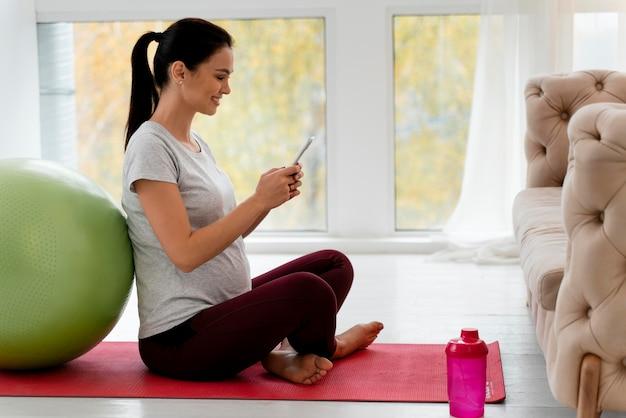 Schwangere frau, die ihr telefon während des trainings überprüft