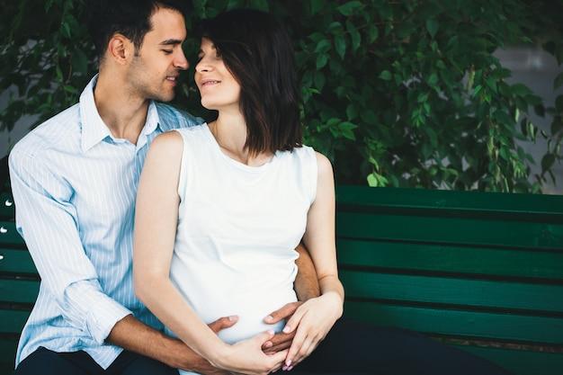 Schwangere frau, die ihre ehemannhände berührt