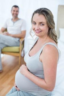 Schwangere frau, die ihren bauch beim sitzen auf stuhl berührt