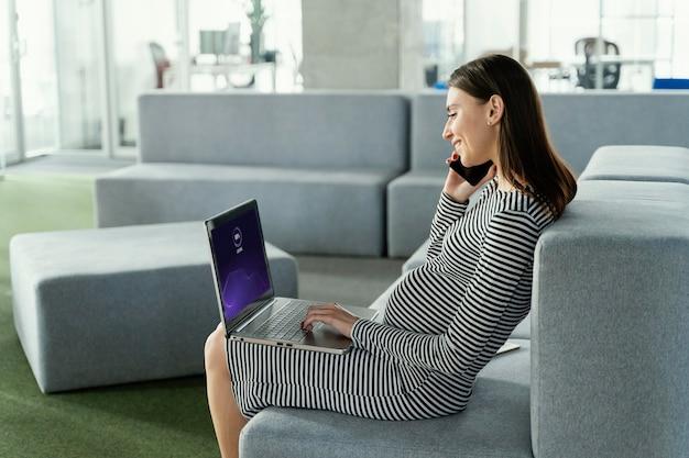 Schwangere frau, die im büro arbeitet