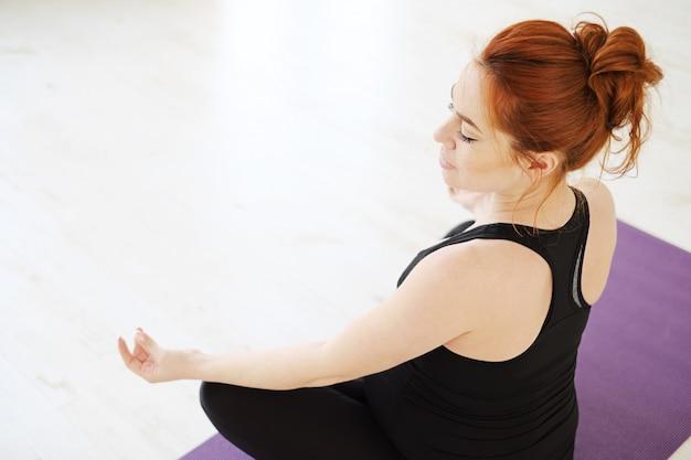 Schwangere frau, die im lotus sitzt, posiert meditation