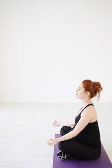 Schwangere frau, die im lotussitz sitzt, entspannt sich