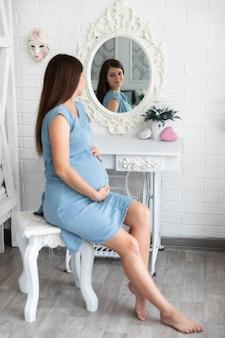 Schwangere frau, die im spiegel sich aufpasst
