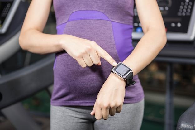 Schwangere frau, die intelligente uhr auf die turnhalle zeigt