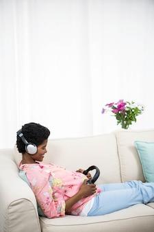 Schwangere frau, die kopfhörer auf bauch auf couch hält