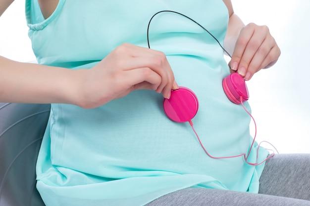 Schwangere frau, die kopfhörer auf bauch hält