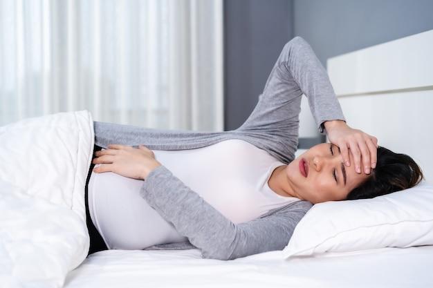 Schwangere frau, die kopfschmerzen leidet, die in einem bett liegen