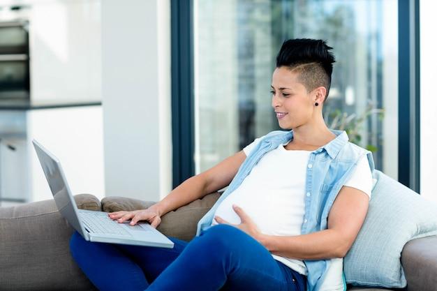 Schwangere frau, die laptop bei der entspannung auf sofa im wohnzimmer verwendet