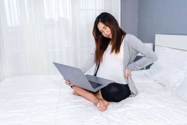 Schwangere frau, die laptop-computer benutzt und rückenschmerzen in einem schlafzimmer leidet