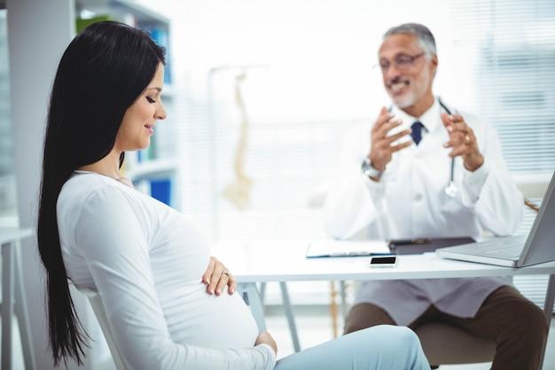 Schwangere frau, die mit doktor an der klinik für gesundheitsüberprüfung sitzt