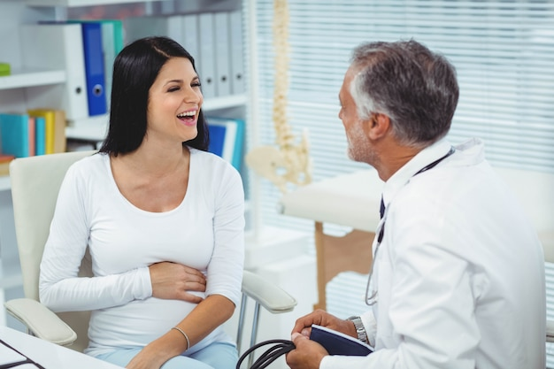 Schwangere frau, die mit doktor in der klinik spricht